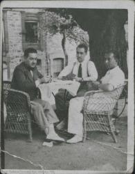 Fotografía de grupo. Tres hombres sentados jugando a las cartas.